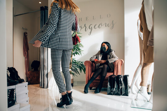 Young blond woman showing an outfit to her african female friend at the interior of a fashion boutique asking for advice. Black woman is sitting on a couch inside a fashion retail store