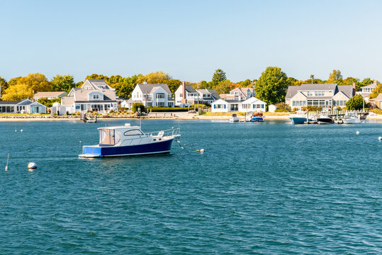 Empty boat moored off  a coast lined with residential buildings with private wooden jetties on a clear autumn day. Hyannis, Cape Cod, MA, USA.