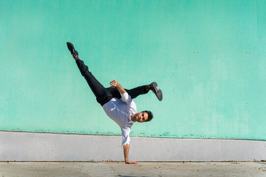 Businessman doing handspring in front of green wall