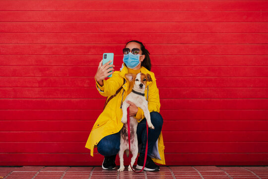 Woman with face mask and dog, taking smartphone selfies in front of red wall