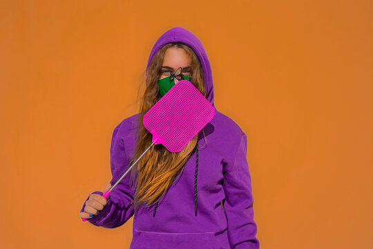 Teenage girl wearing protective face mask with fly sticker, holding swatter