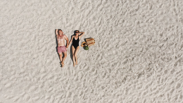 Aerial view of a young couple lying on the white beach sand. man and woman in swimwear spend time together and travel through the desert