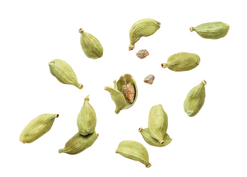 Cardamom pods whole and chopped fly on a white background. Isolated