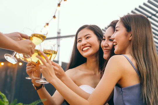 happy asian woman teenagers cheering and toast with white sparkling wine glass to celebrating at dinner party in summertime. celebration, relationship and friendship concept.