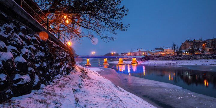 uzhhorod, ukraine - 26 DEC 2016: winter cityscape at dawn. beautiful scenery on the river uzh. city lights reflecting in the water. snow on the embankment