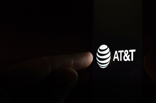 AT&T logo on a smartphone screen in a dark room and a finger touching it.