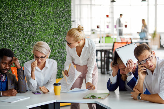 angry female chef scolds employees for a poor result at the end of month, scream and shout in the office, diverse workers sit afraid of her