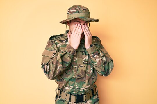 Young caucasian man wearing camouflage army uniform rubbing eyes for fatigue and headache, sleepy and tired expression. vision problem