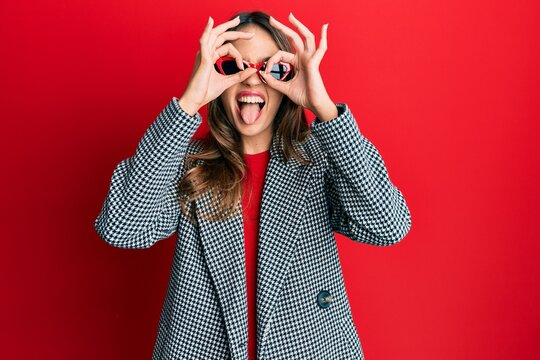 Young brunette woman wearing fashion and modern look doing ok gesture like binoculars sticking tongue out, eyes looking through fingers. crazy expression.