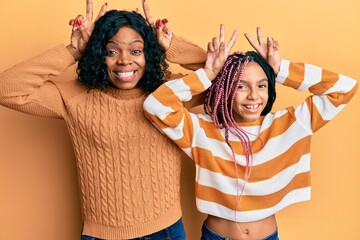 Beautiful african american mother and daughter wearing wool winter sweater posing funny and crazy with fingers on head as bunny ears, smiling cheerful