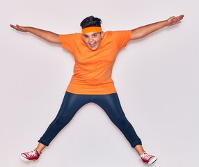 Adorable hispanic kid wearing sportswear smiling happy. Jumping with smile on face over isolated...