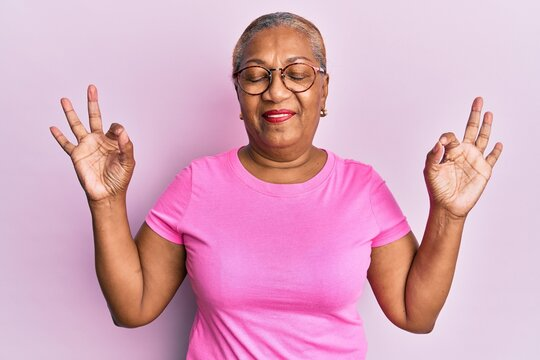 Senior african american woman wearing casual clothes and glasses relax and smiling with eyes closed doing meditation gesture with fingers. yoga concept.