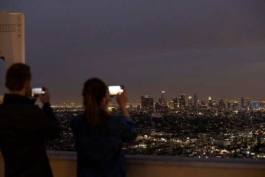 People use their mobile phones at sunset from Griffith Observatory with the downtown skyline during a partial lockdown during the outbreak of the coronavirus disease (COVID-19), in Los Angeles