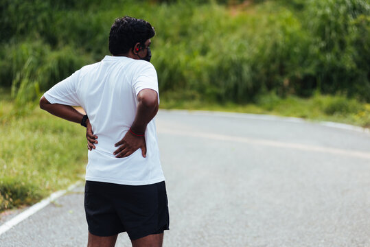Close up Asian young sport runner black man wear watch feel pain on his spine low back and hip while running at the outdoor street health park, healthy exercise Injury from workout concept