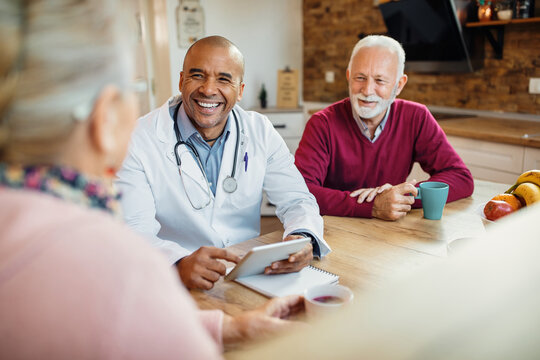 Happy African American doctor talking to senior couple during home visit.