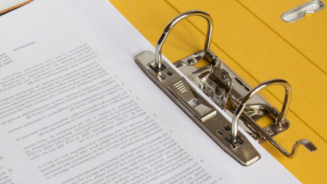 Open yellow binder close up, stack of white papers and bright metal rings