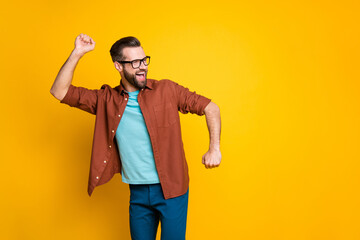Photo of funky positive brown haired young man raise fists dancer empty space isolated on yellow color background Wall mural