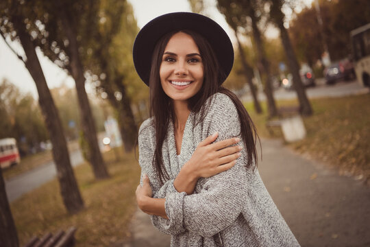 Photo portrait of pretty girl smiling embracing herself in cold autumn weather on city streets wearing grey casual outfit