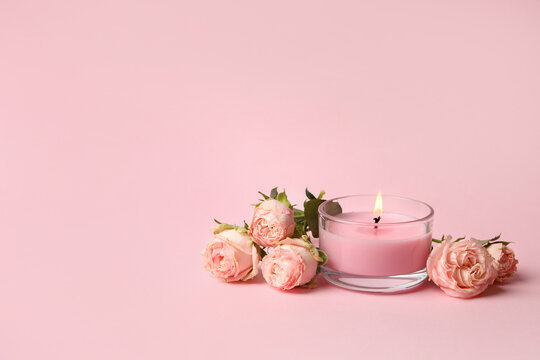 Scented candle and roses on pink background