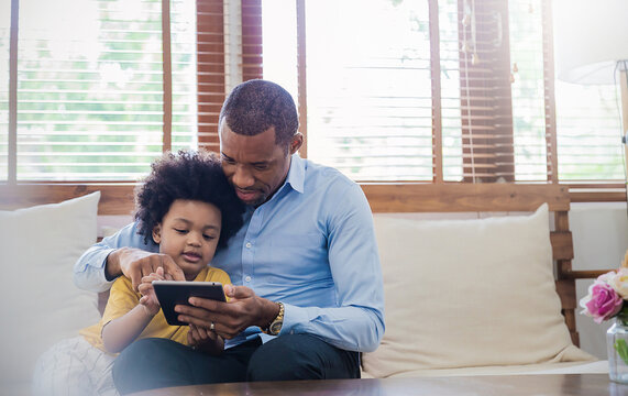 Portrait of american african father and son using gadget learning at home. Daddy and his little boy spending leisure time at home. Single dad, family lifestyle father's day concept
