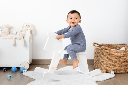 Smiling baby on rocking horse in playroom