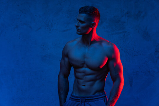 Muscular man posing in the colorful light
