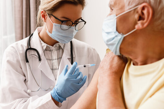 Doctor injecting vaccine to elderly man during home visit