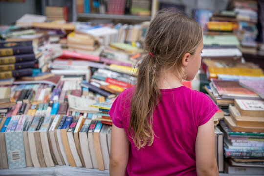 Girl looking at books for sale on a street market in China