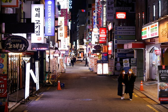 Women walk on an empty street affected by heightened social distancing rules amid the coronavirus disease (COVID-19) pandemic in Seoul