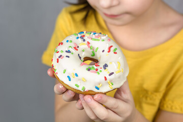 close up of hands hold a glazed white doughnut