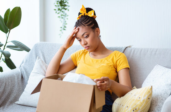 Sad young lady unpacking wrong parcel, delivery mistake