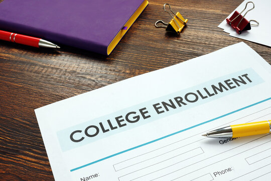 College enrollment application on the wooden surface and notepad.