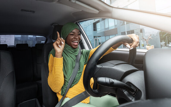 Happy muslim black female driver singing and dancing while driving car