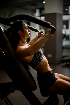 Close-up view of beautiful brunette woman doing exercises on the simulator in fitness club.