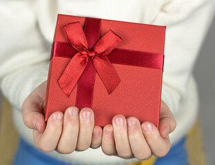 Close up of child hands gift a small gift box wrapped with red ribbon and bow.