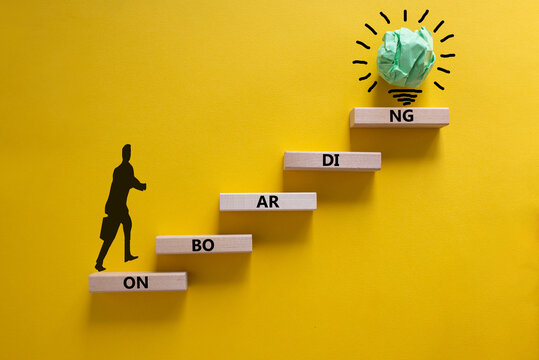 Success onboarding process symbol. Wood blocks stacking as step stair on yellow background, copy space. Businessman icon and light bulb. Word 'onboarding'. Business and onboarding concept.