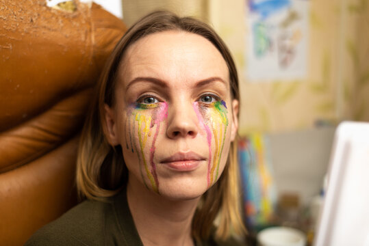 Bad makeup concept. Woman with multi-colored tears from paints.