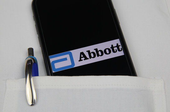 Viersen, Germany - April 9. 2020: Close up of mobile phone screen with logo lettering of Abbott Sandoz pharmaceutical company in pocket of white doctors coat with pencil