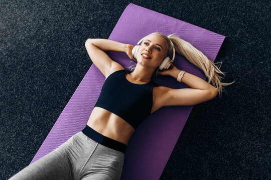 Fitness workout, top view, young sportive woman listens to music in headphones and does exercises on the press, in the gym