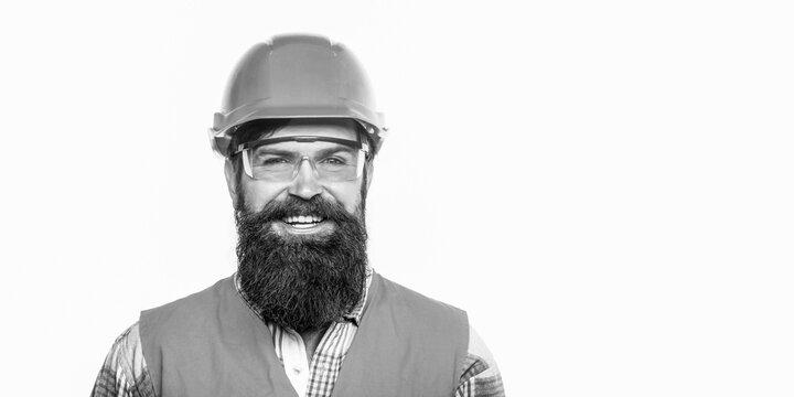 Builder in hard hat, foreman or repairman in the helmet. Portrait of a builder smiling. Bearded man worker with beard in building helmet or hard hat. Building glasses. Copy space