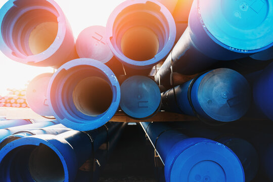 Big Blue Plastic PVC Water and Drain Pipes in sunlight.