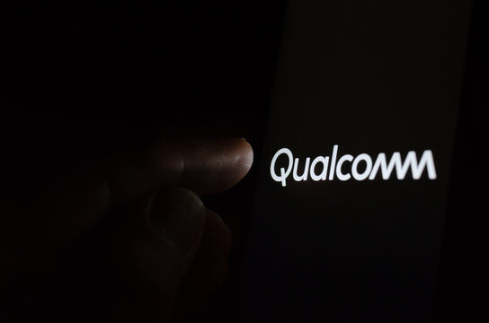 Qualcomm chip design company logo on a glowing screen and a hand pointing at it.
