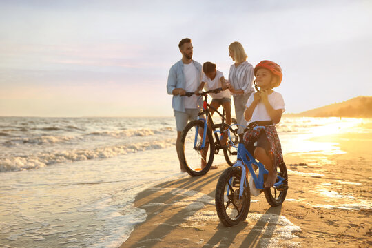 Happy family with bicycles on sandy beach near sea