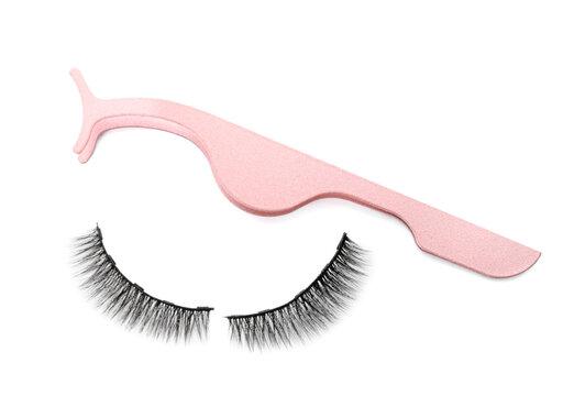 Magnetic eyelashes and tweezers on white background