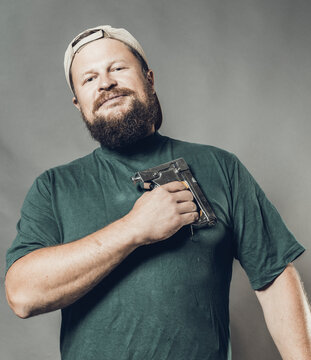 Joyful bearded craftsman in green t-shirt having fun with staple gun