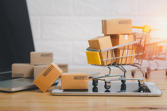 Brown paper boxs in shopping cart with laptop on wood table in office background.Easy shopping with finger tips for consumers.Online shopping and delivery service concept.