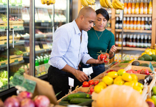 Positive latin american family couple looking for ripe organic tomatoes in food store