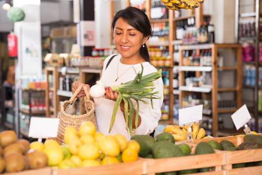 Woman choosing fresh greens in supermarket
