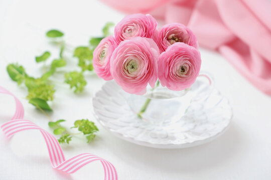 Bouquet of pink ranunculus flowers in glass cup.  ピンクのラナンキュラス