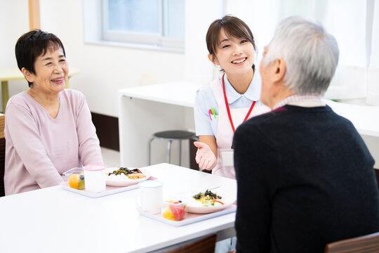 食事中の高齢の入居者たちと介護施設の女性職員